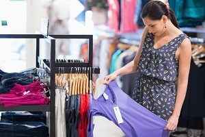 Woman is looking at price tag of purple shirt in shopping mall