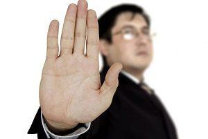 hombre-de-negocios-con-traje-y-gafas-levantando-su-mano-en-senal-de-stop